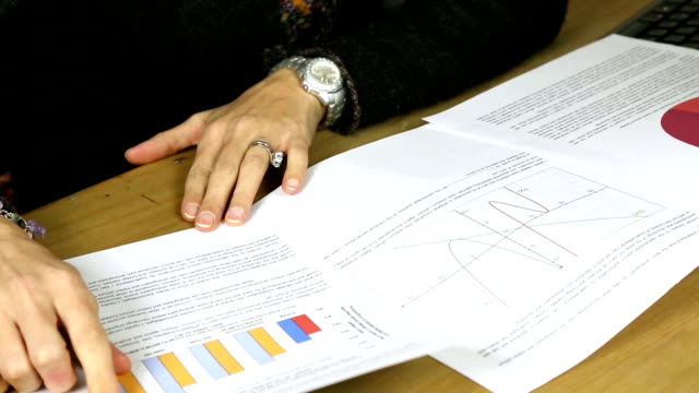 attractive female hispanic business executive looking at graphs and statistics - archivista video stock e b–roll