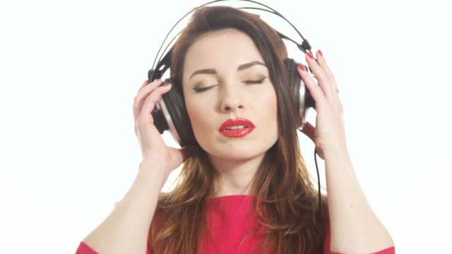 vidéos et rushes de attractive female in red t-shirt dancing to the music in big headphones notices the camera and send an air kiss isolated on white background close up - rouge à lèvres rouge