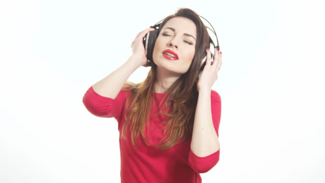 vidéos et rushes de attractive female in red t-shirt dancing to the music in big headphones notices the camera and send an air kiss isolated on white background medium shot - rouge à lèvres rouge