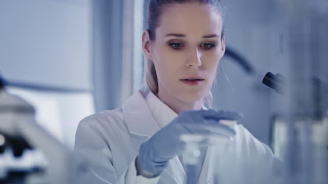 attractive female microbiologist during research. using microscope in futuristic lab - biologist stock videos & royalty-free footage