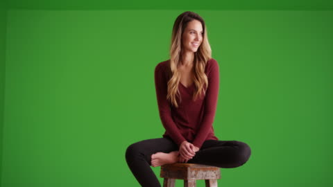 attractive female millennial looking off camera and smiling on green screen - sitting stock videos & royalty-free footage