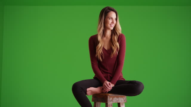 vídeos de stock e filmes b-roll de attractive female millennial looking off camera and smiling on green screen - cadeira