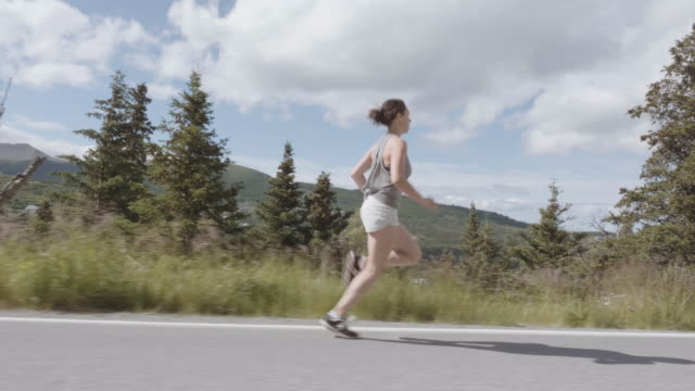 uhd 4k slomo: attractive female runner on a scenic highway in the mountains - anchorage alaska stock videos and b-roll footage