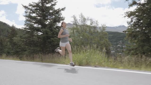 UHD 4K SLOMO: attraktive weibliche Läufer auf einer malerischen Autobahn in den Bergen