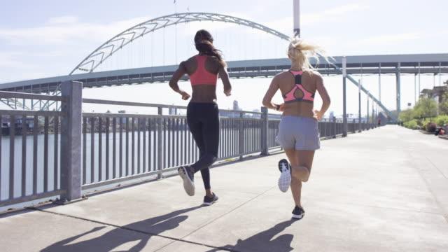 Attraktiva kvinnliga löpare i staden längs vattnet