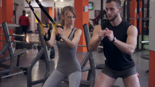 vídeos de stock e filmes b-roll de attractive fit woman working with instructor and battle ropes at gym - instrutor