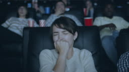 Attractive girl feeling scared during horror film in dark modern cinema