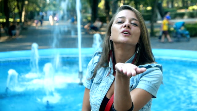 Attractive girl standing in front of a fountain and sending kisses to camera