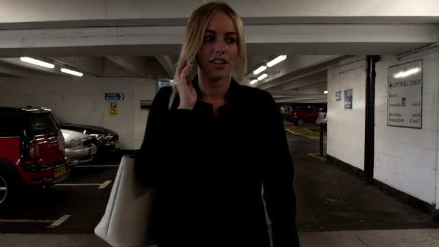 Attractive good looking young blonde business woman angry phone call cellphone mobile alone car park parking garage