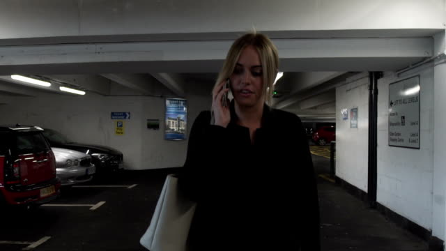 attractive good looking young blonde business woman happy phone call cellphone mobile smiling parking garage car park - 立体駐車場点の映像素材/bロール
