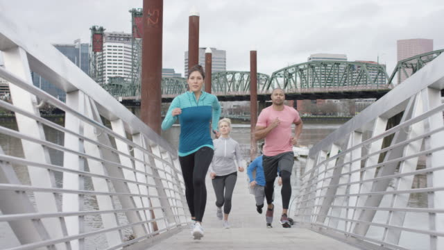 attractive group of runners ascending a ramp on the waterfront - allenatore video stock e b–roll