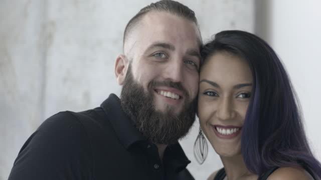 vidéos et rushes de attractive, happy couple kiss and look into camera - embrasser sur la bouche