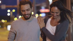 Attractive Happy Couple Walking on Streets of Night Town