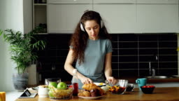 Attractive happy girl in headphones dancing and and listening to music while cooking healthy vegeatable salad in the kitchen at home at morning