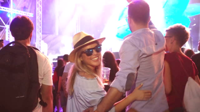 Attractive hipster woman dancing on festival with friends
