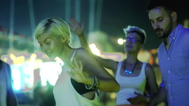 魅力的な流行に敏感な女性の友達と祭りに踊り - 灯台船点の映像素材/bロール