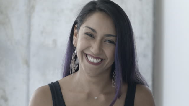 Attractive hispanic woman smiling and laughing towards camera