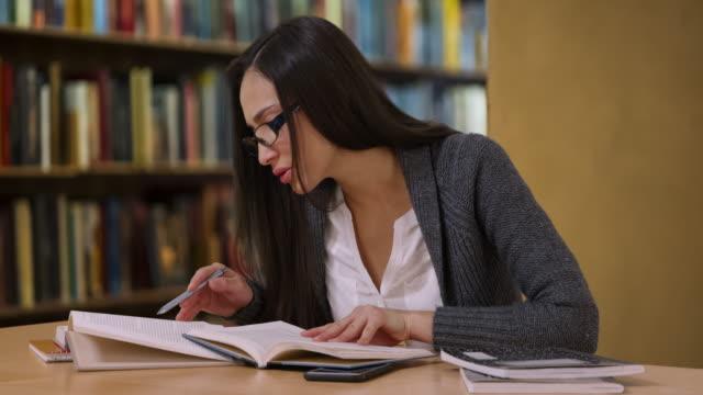 vídeos de stock e filmes b-roll de attractive hispanic woman with glasses reads book at the library - óculos de leitura
