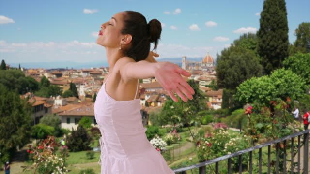 vidéos et rushes de attractive latina woman in sundress tilts her face to sun and twirls in florence - robe d'été