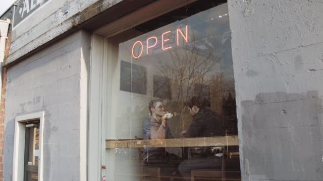 Attractive male couple in coffee shop window