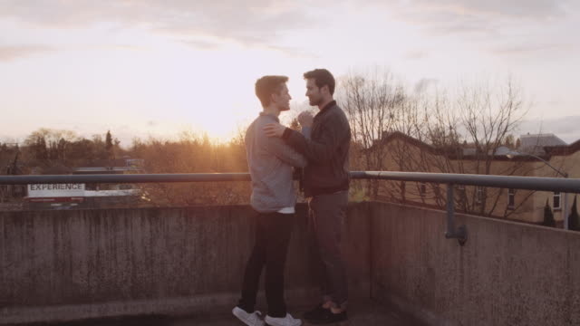 attractive male couple on top of a parking structure during sunset - bisexuality stock videos and b-roll footage