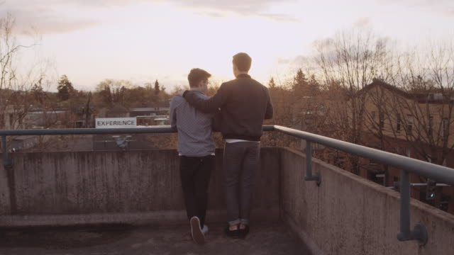 attractive male couple on top of a parking structure - bisexuality stock videos and b-roll footage
