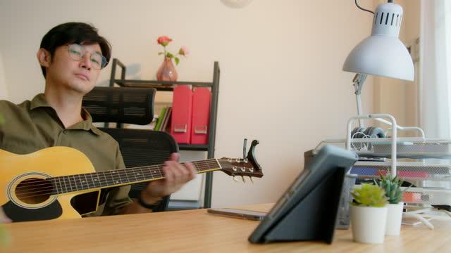 魅力的な男デジタルタブレット上のビデオ通話を介して教師とギターのeラーニングクラスを演奏学習。 - シンガーソングライター点の映像素材/bロール