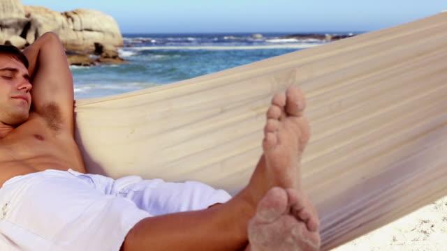 vídeos de stock e filmes b-roll de attractive man napping in a hammock - napping