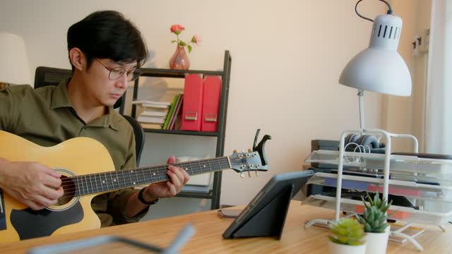 デジタルタブレット上のオンラインクラスを介してギターを練習魅力的な男 - シンガーソングライター点の映像素材/bロール