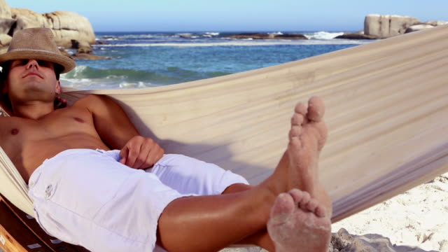 attractive man relaxing in a hammock - sdraiato video stock e b–roll