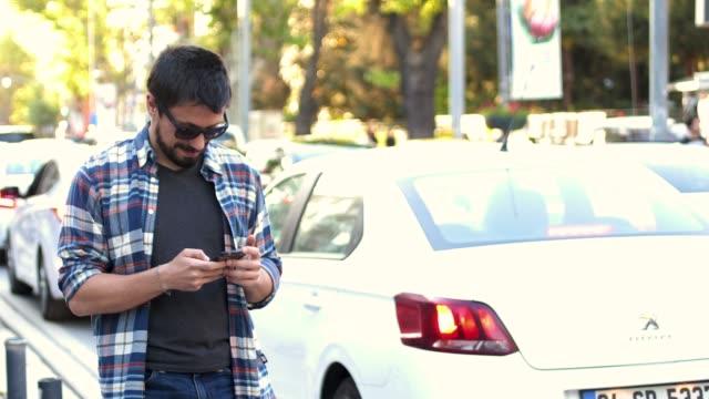 vídeos y material grabado en eventos de stock de hombre atractivo utilizando el teléfono móvil durante la caminata en las calles - letra x
