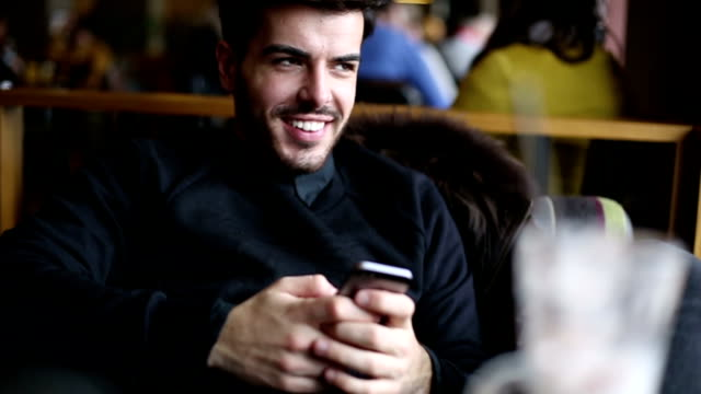 Attractive man using smartphone in the coffee shop