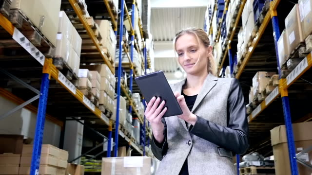 attractive manager working on tablet in warehouse - examining stock videos & royalty-free footage
