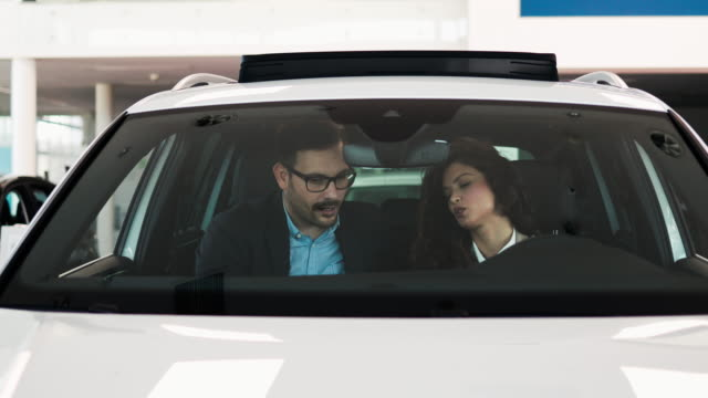 attractive middle age couple buying car in showroom - car showroom stock videos & royalty-free footage