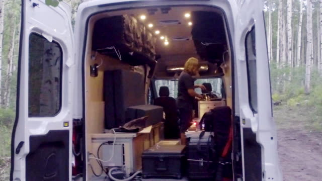 attractive middle-aged woman cooking in a camper van conversion - camper van stock videos & royalty-free footage