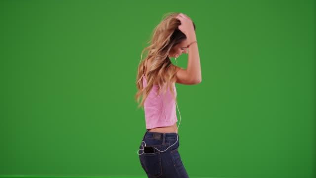 stockvideo's en b-roll-footage met attractive millennial girl dancing on green screen - in ear koptelefoon