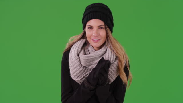 vídeos de stock, filmes e b-roll de attractive millennial girl wearing beanie, scarf, and gloves on green screen - agasalho