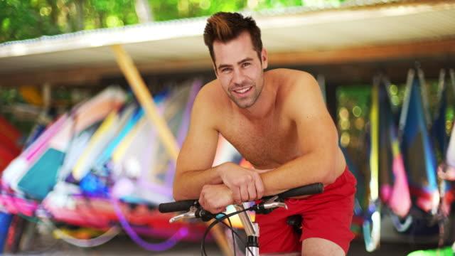 stockvideo's en b-roll-footage met attractive millennial guy sitting on bike smiling at camera - ontbloot bovenlichaam