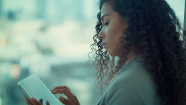 attractive, mixed race businesswoman using tablet standing near window in office. - profile stock videos & royalty-free footage
