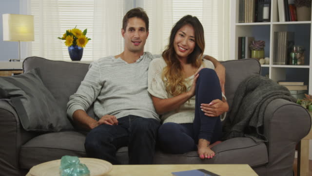 Attractive mixed race couple sitting on couch smiling