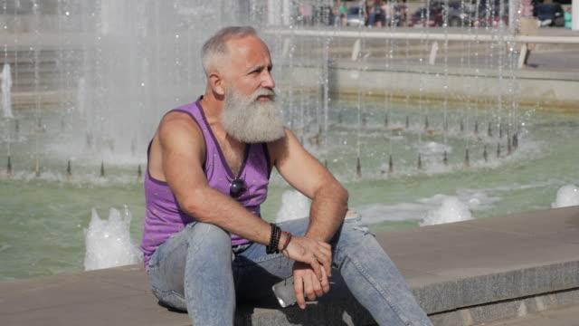 vídeos de stock, filmes e b-roll de homem mais velho atraente descansando sentada perto da fonte - 50 59 years