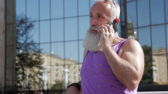 スマート フォンで話している魅力的な年上の男 - 50 59 years点の映像素材/bロール
