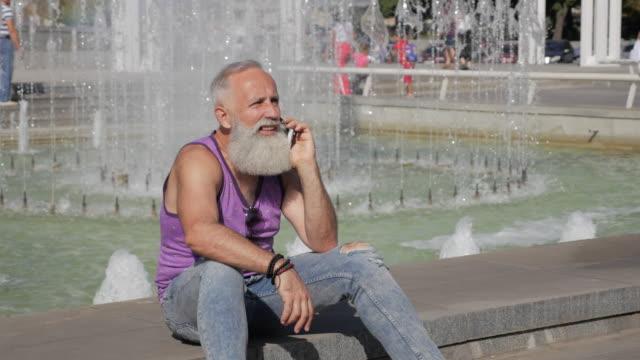 vídeos de stock, filmes e b-roll de homem mais velho atraente falando no smartphone - 50 59 years