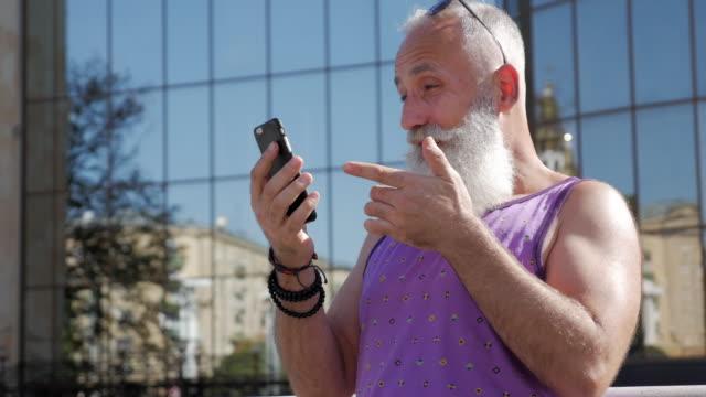 魅力的な年上の男がビデオで話をするスマート フォンを使用してください。 - 50 59 years点の映像素材/bロール