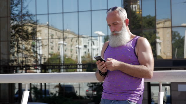 魅力的な年上の男は、メッセージのスマート フォンを使用してください。 - 50 59 years点の映像素材/bロール