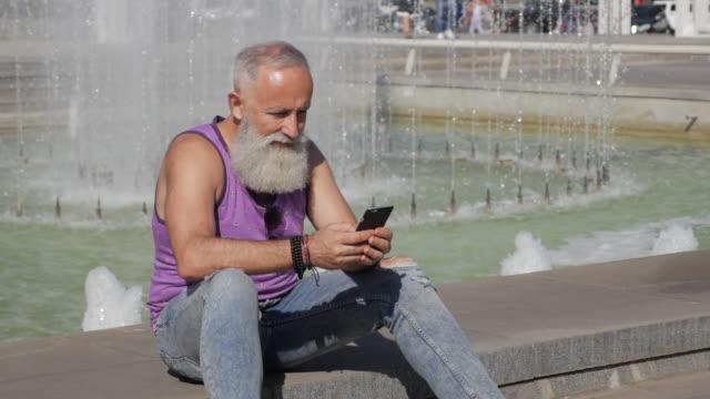vídeos de stock, filmes e b-roll de homem mais velho atraente usa o smartphone para mensagens - 50 59 years
