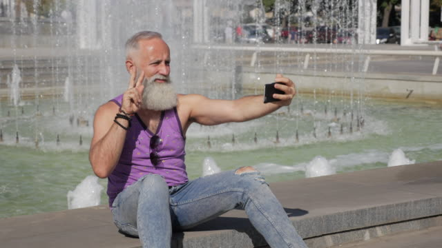 attractive older man uses smartphone for selfie - cool attitude stock videos & royalty-free footage