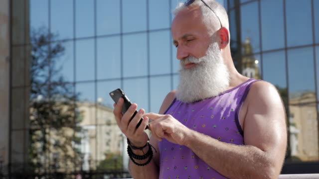 vídeos de stock, filmes e b-roll de homem mais velho atraente usa o smartphone para ver as fotos - 50 59 years