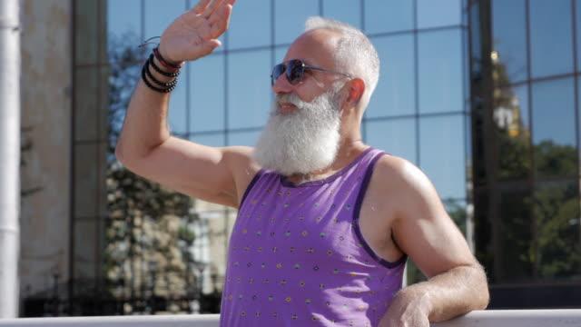 魅力的な年上の男は、挨拶と笑顔で手を振ってください。 - 50 59 years点の映像素材/bロール