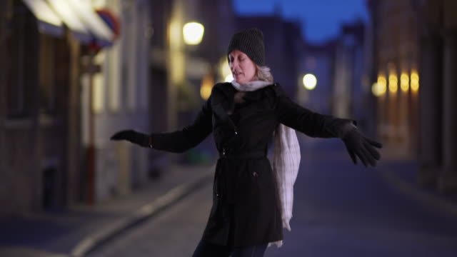 attractive older woman in winter dancing at night on european city street - winter coat stock videos & royalty-free footage